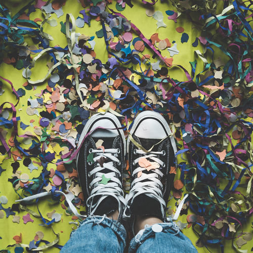 Feet seen from above on a floor full of colorful confetti