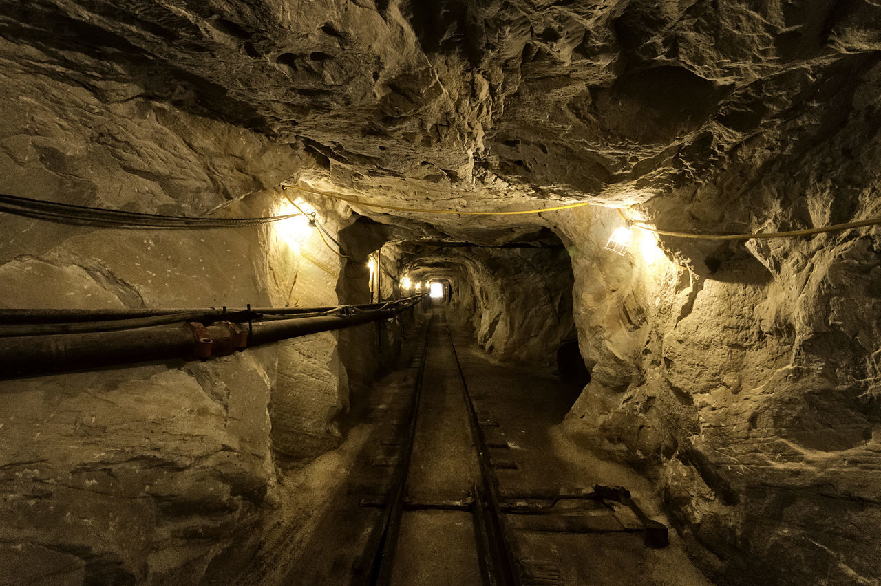 illuminated, tunnel, architecture, indoors, lighting equipment, the way forward, direction, built structure, cave, no people, mine, staircase, subway, railing, night, mining, steps and staircases, wall, wall - building feature, industry, light, ceiling, light at the end of the tunnel