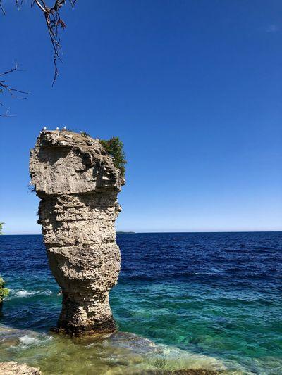 Rocks on sea shore against clear blue sky