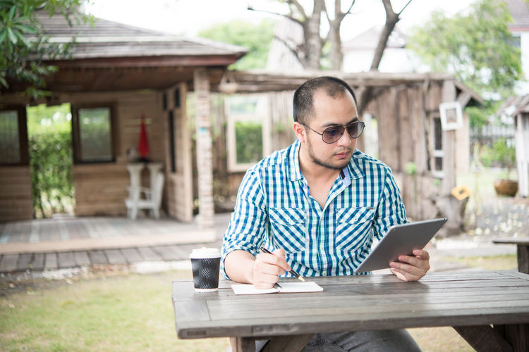 Man With Disposable Cup Using Digital Tablet Outdoors
