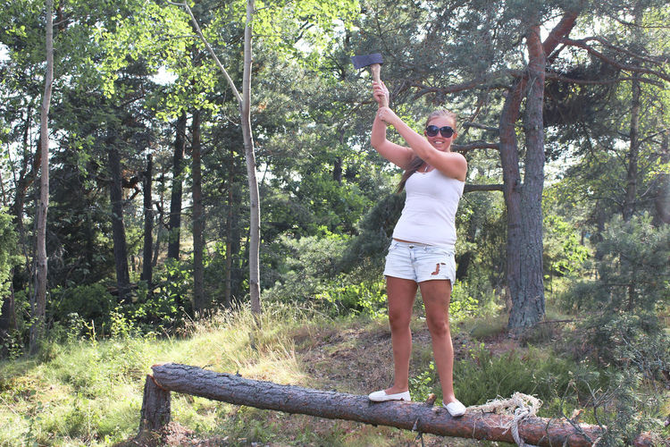 Woman with axe standing on tree in forest