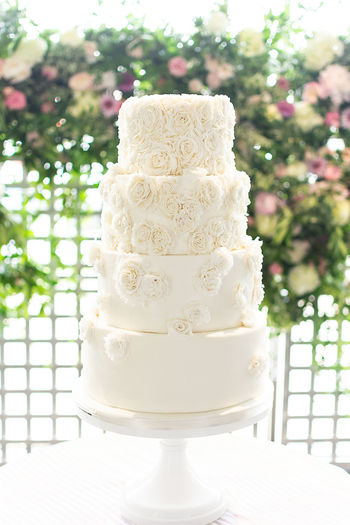 4 tier wedding cake with rosette embellishments and floral background. Bright Romantic Textured  Tier Baked Bakery Bride Cake Celebration Dessert Flower Food Food And Drink Indulgence Marrage Rosettes Rosé Sweet Sweet Food Temptation Trend Wedding Wedding Cake Wedding Cake Figurine White Color