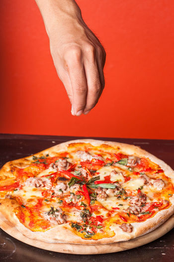 Business Cheese Dairy Product Dinner Edible Mushroom Fast Food Restaurant Food Food And Drink Hand Human Body Part Human Hand Indoors  Italian Food Lunch Meal Mozzarella Pepperoni Pizza Pizzeria Restaurant Tomato Tomato Sauce Unhealthy Eating Vegetable