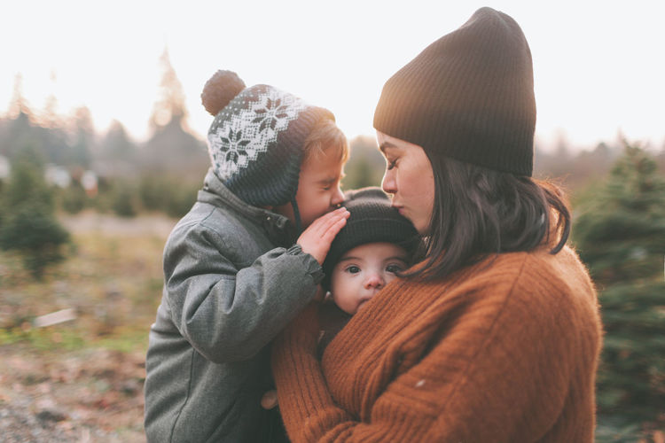 A mother and son kissing a baby in winter. Togetherness Bonding Family Child Emotion Love Baby Parent Mother Son Warm Clothing Outdoors Kiss Winter Human Connection