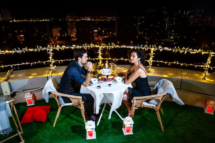 Young Couple Having Dinner On Illuminated Terrace At Night