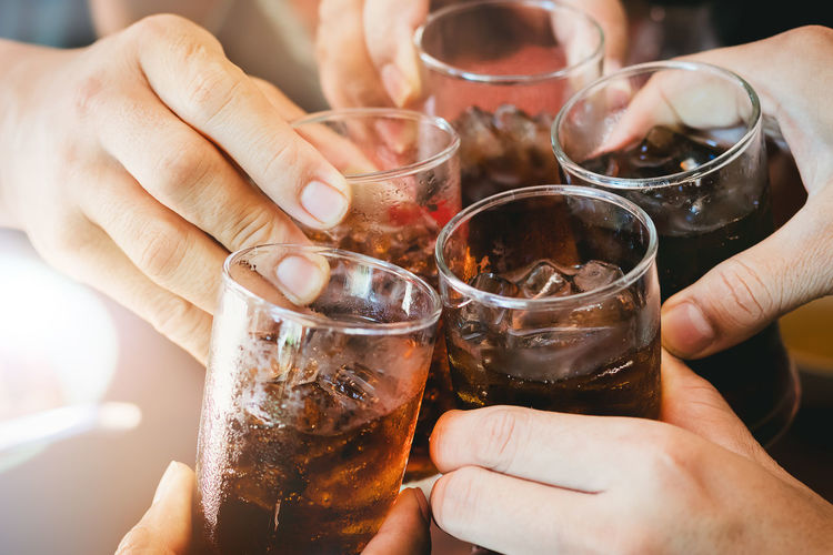 Cropped Hands Of People Toasting Drinks