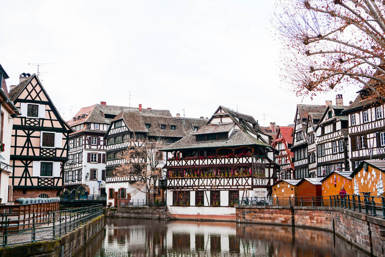 Buildings by river against sky in city