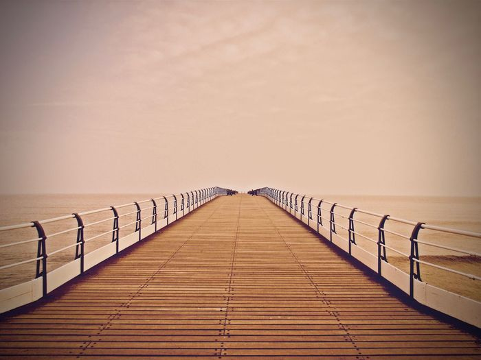 Wooden Footbridge Over Sea Against Clear Sky