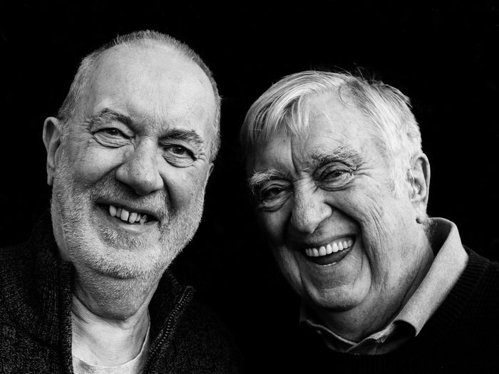 Portrait Of Smiling Senior Men Against Black Background