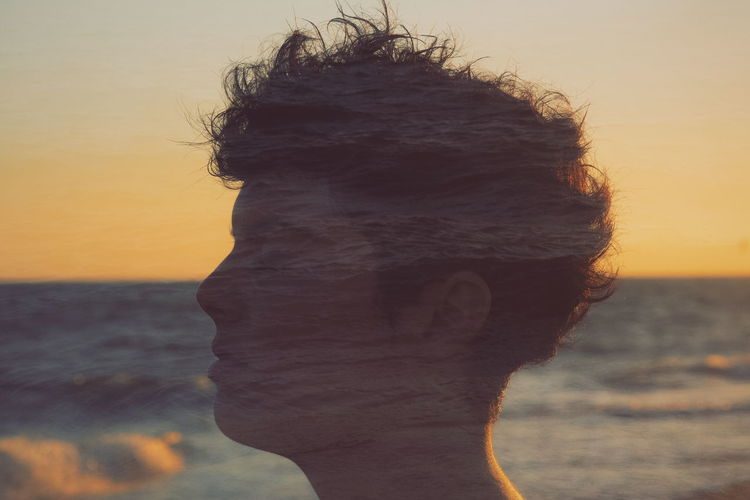 Close-up portrait of woman against sea during sunset