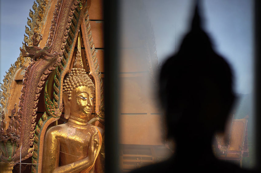 Silhouetted buddha with Giant golden Buddha at the Tiger Cave Temple in Kanchanburi Buddha Buddism Focus On Foreground Gold Gold Colored Golden Monument Religion Religions Sculpture Selective Focus Shadow Sillouette Statue Temple Thailand Tourism Tourist Attraction  Traveling Wanderlust Window