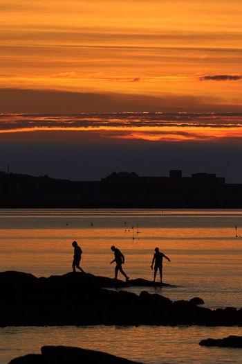 Silhouette people on beach against orange sky
