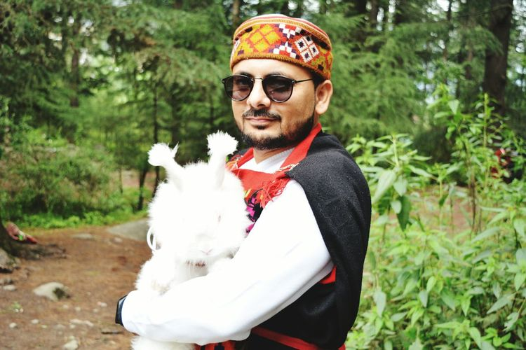 Portrait of young man wearing traditional clothes while holding rabbit outdoors