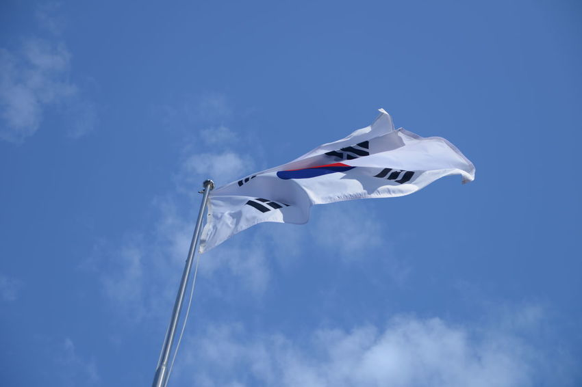 Sky Low Angle View Flag Patriotism Wind Cloud - Sky Nature Blue No People Day Environment Waving Motion Pole White Color Outdoors Flying Pride Mode Of Transportation Plane Korean Flag