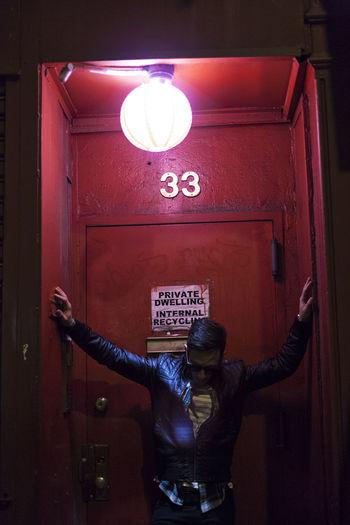 Man standing on illuminated door of building