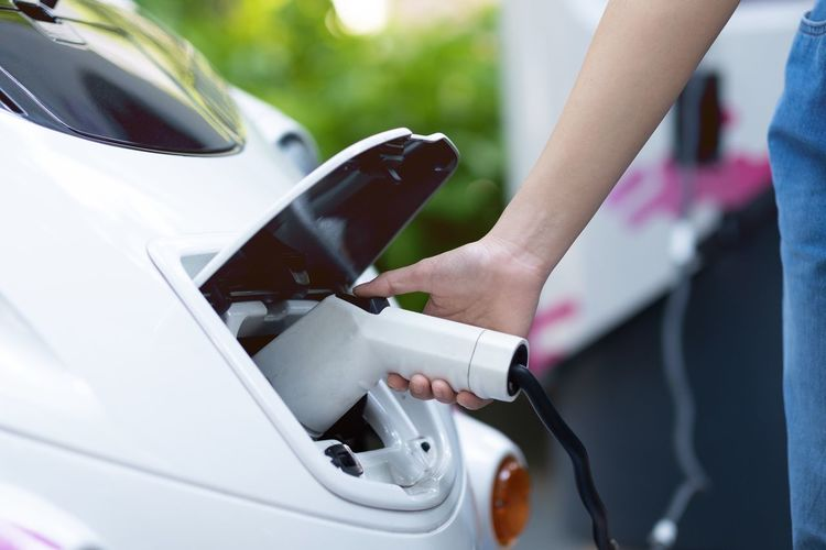 Midsection of woman charging electric car