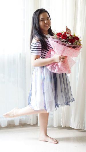 Full length of smiling girl standing at home