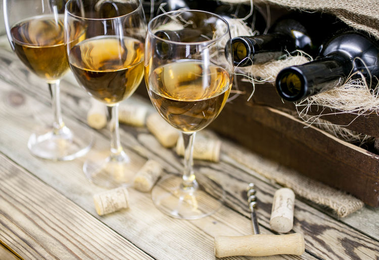 Three Glasses Of White Wine On A Wooden Background Alcohol Close-up Corkscrew Drink Drinking Glass Food Food And Drink Glass Glass - Material Household Equipment No People Still Life Table White Wine Wine Wineglass Wood - Material