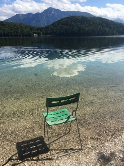 Empty chairs by lake against mountains