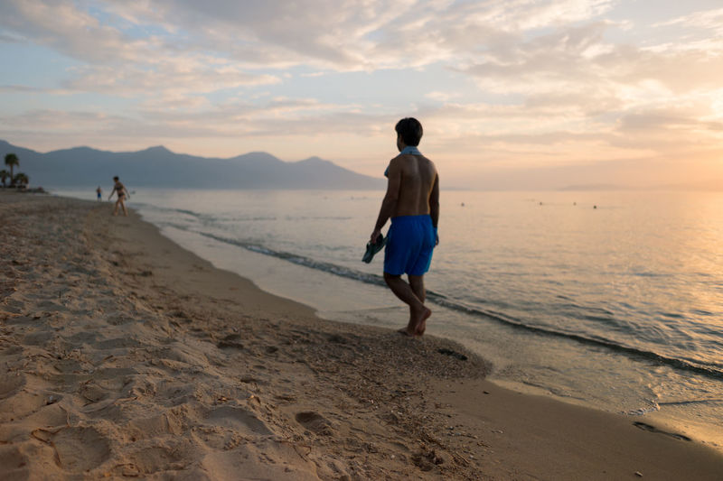Walking on the Beach During Sunset. (close range focus shallow depth of field) Beach Beauty In Nature Cloud - Sky Clouds And Sky Dramatic Sky Full Length Idyllic Leisure Activity Lifestyles Man Enjoy The New Normal Nature People And Places Remote Sand Scenics Sea Sky Sunset Tranquil Scene Tranquility Vacations Walking Walking Alone... Walking On The Beach My Year My View Moments Of Happiness It's About The Journey