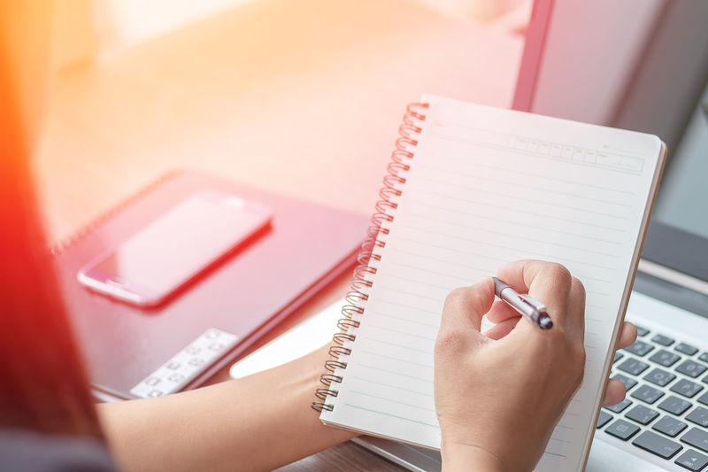 Midsection of businesswoman writing on spiral notebook by laptop in office