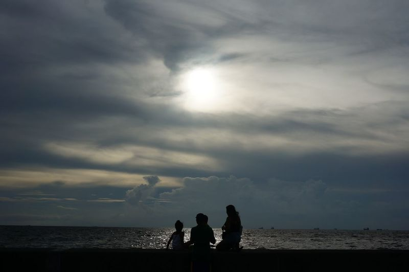 Silhouette of couple sitting on beach