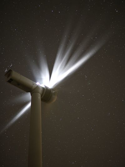 Low angle view of windmill against star field at night