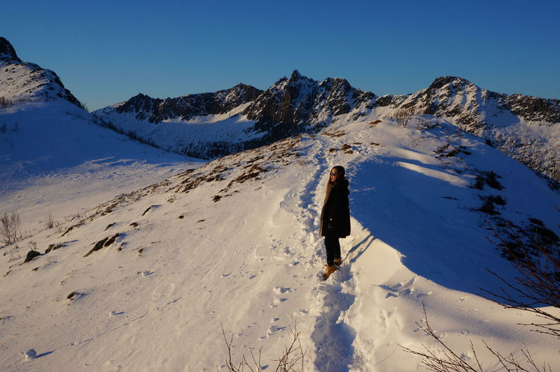 Full Length Of Woman Standing On Snow Covered Mountain