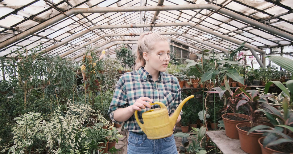 Caucasian woman standing in greenhouse