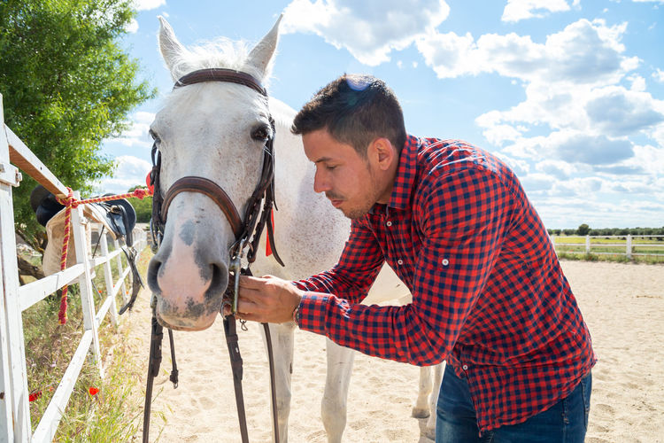 Mid adult man standing with horse