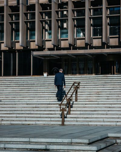 Rear view of man on staircase in city