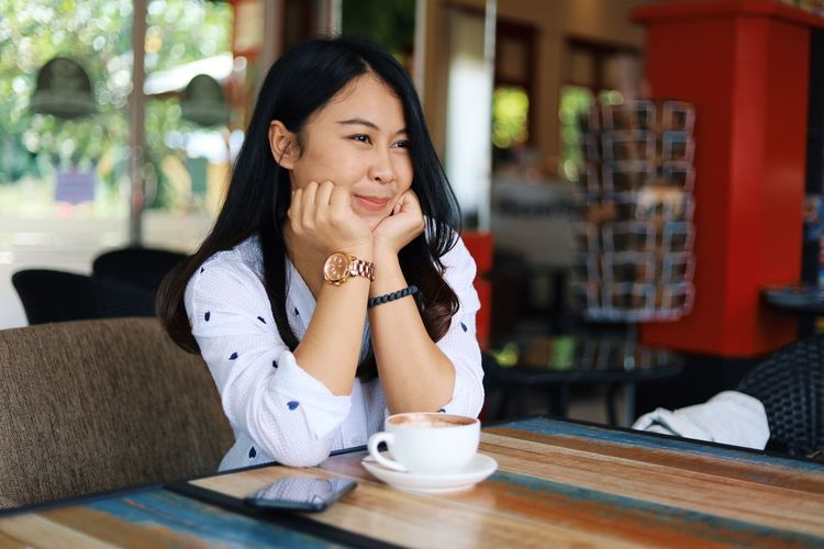 One Person Sitting Young Adult Women Young Women Smiling Adult Table Food And Drink Lifestyles Real People Waist Up Indoors  Casual Clothing Front View Leisure Activity Beautiful Woman Drink Cafe Hair Hairstyle