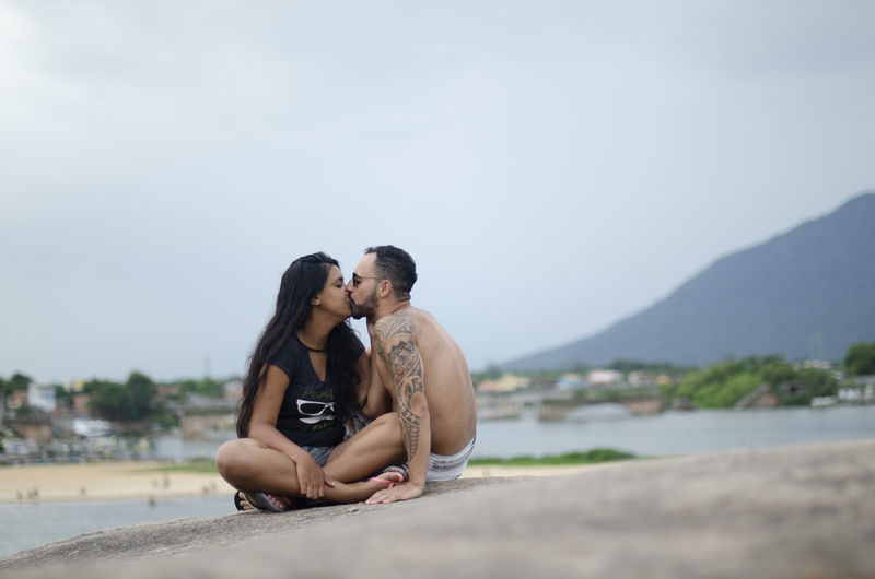 Couple kissing while sitting on beach against sky