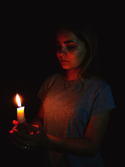 Woman Holding Burning Candle In Darkroom