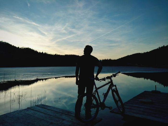 Rear View Of Silhouette Man With Bicycle Standing On Pier Over Lake
