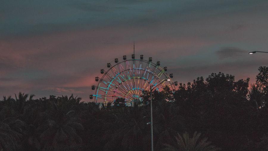 Illuminated ferris wheel against sky at dusk
