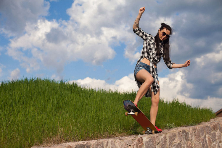 Young woman in short jeans briefs and long shirt is doing skate trick on the curb on the background of green grass. Human Arm Outdoors Fashion Casual Clothing Vitality Grass Field Young Women Day Motion Nature Young Adult Land Leisure Activity Plant Real People Lifestyles Cloud - Sky Sky One Person Full Length Beauty In Nature