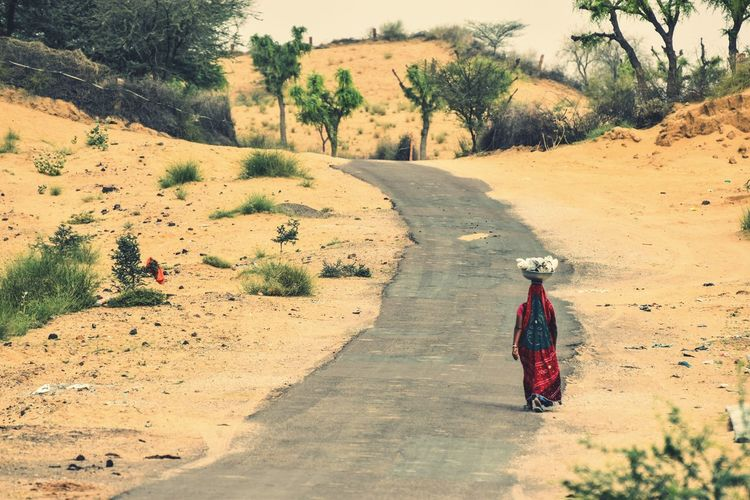 Rear view of woman walking on road at field