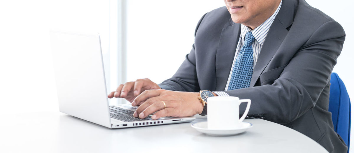 Rear view of man using laptop on table