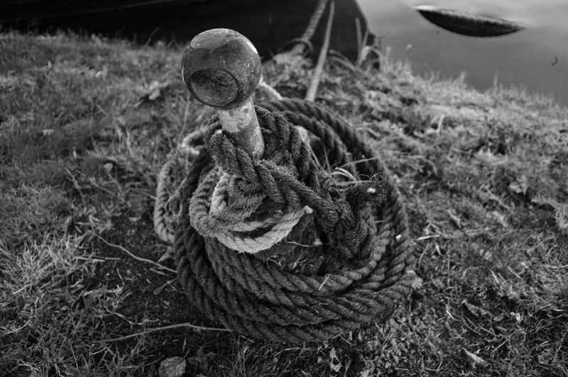 High Angle View Of Tied Rope On Bollard