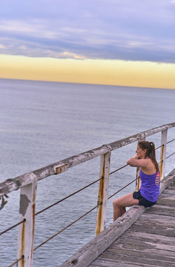 Young Woman Sitting On Pier Against Sky During Sunrise