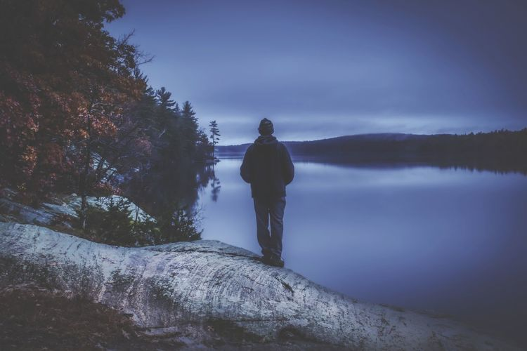 Rear view of man looking at lake against sky during dusk