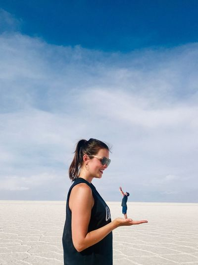Side view of young woman on beach against sky