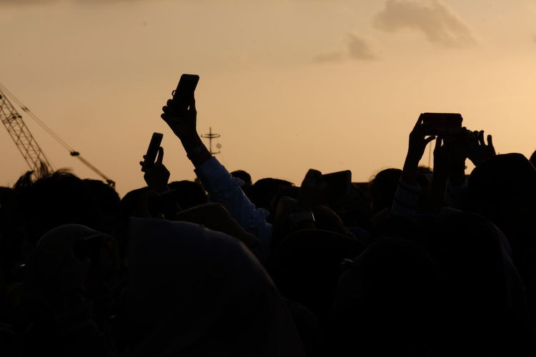 Rear view of silhouette people on smart phone against sky during sunset