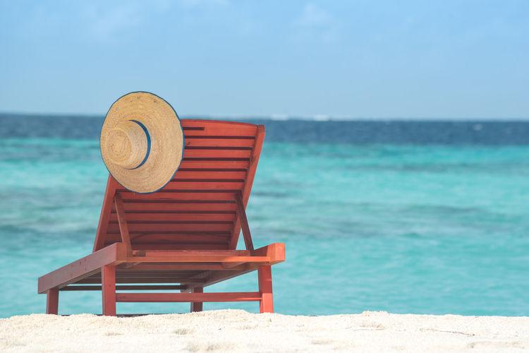 Chair on beach against blue sky