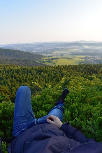 Low section of man relaxing on landscape against sky
