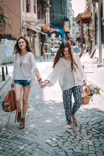 Two hippie women friends walking on a sunny day with a backpack and a basket.  freedom and summer