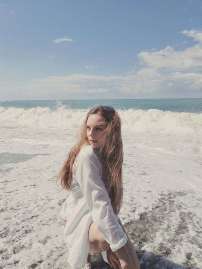 Beautiful young woman on beach against sky