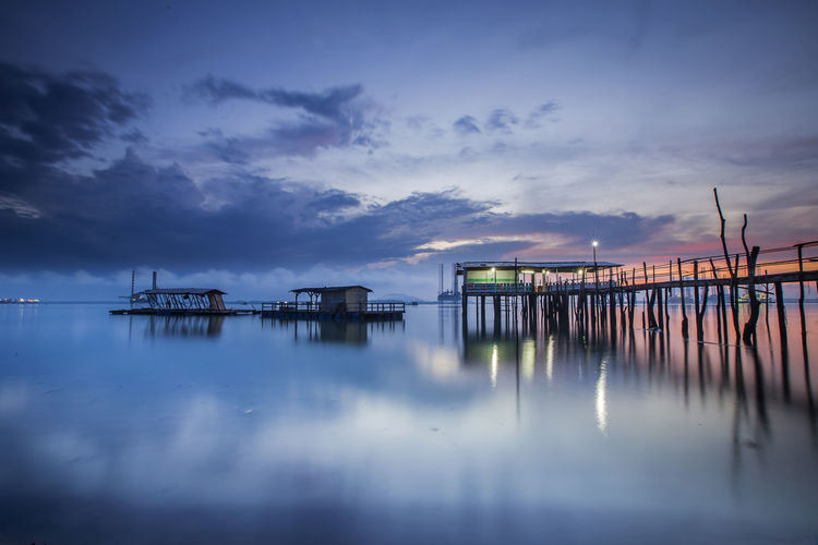 Stilt houses and pier at lake against cloudy sky