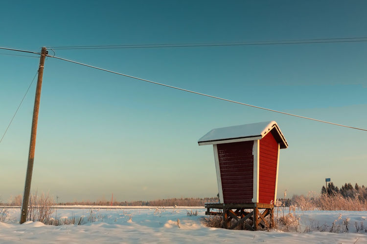 Milk Shelter And A Telephone Pole Architecture Building Exterior Built Structure Cable Clear Sky Cold Temperature Connection Electricity Pylon Finland House No People Outdoors Power Line  Rural Sky Weather Winter